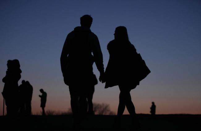 The silhouettes of a couple holding hands at dusk on Parliament Hill, Hampstead Heath, north London.
