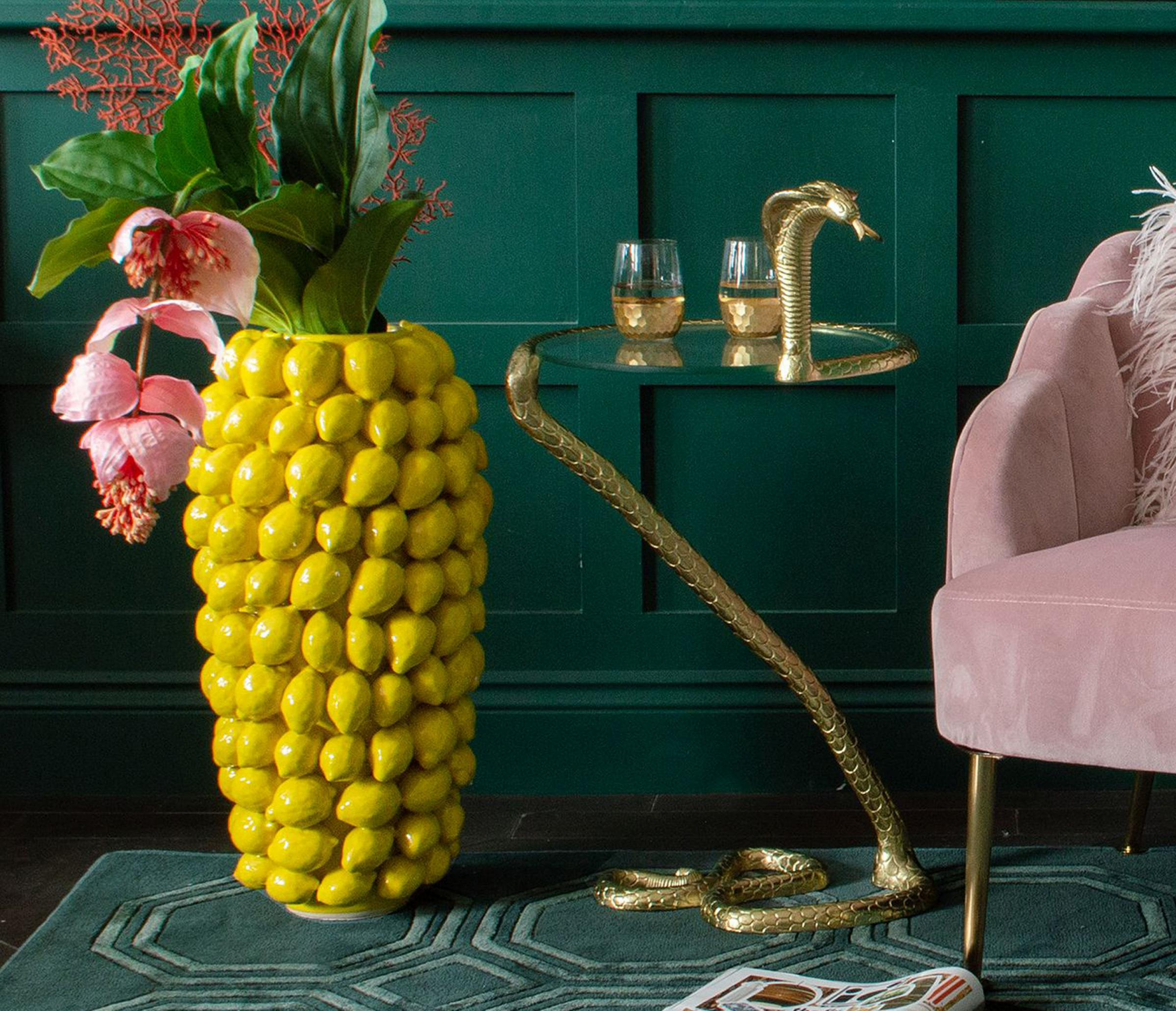 Undated photo of the Cobra brass snake side table, lemon yellow vase, Audenza.  See PA INTERIORS Global Functionality.  Photo credit should read: PA Photo / Audenza.  DISCLAIMER: This image is to be used only to accompany PA Feature INTERIORS Global.
