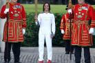 Dame Kelly Holmes holds the Olympic Flame with Beefeaters at the Tower of London