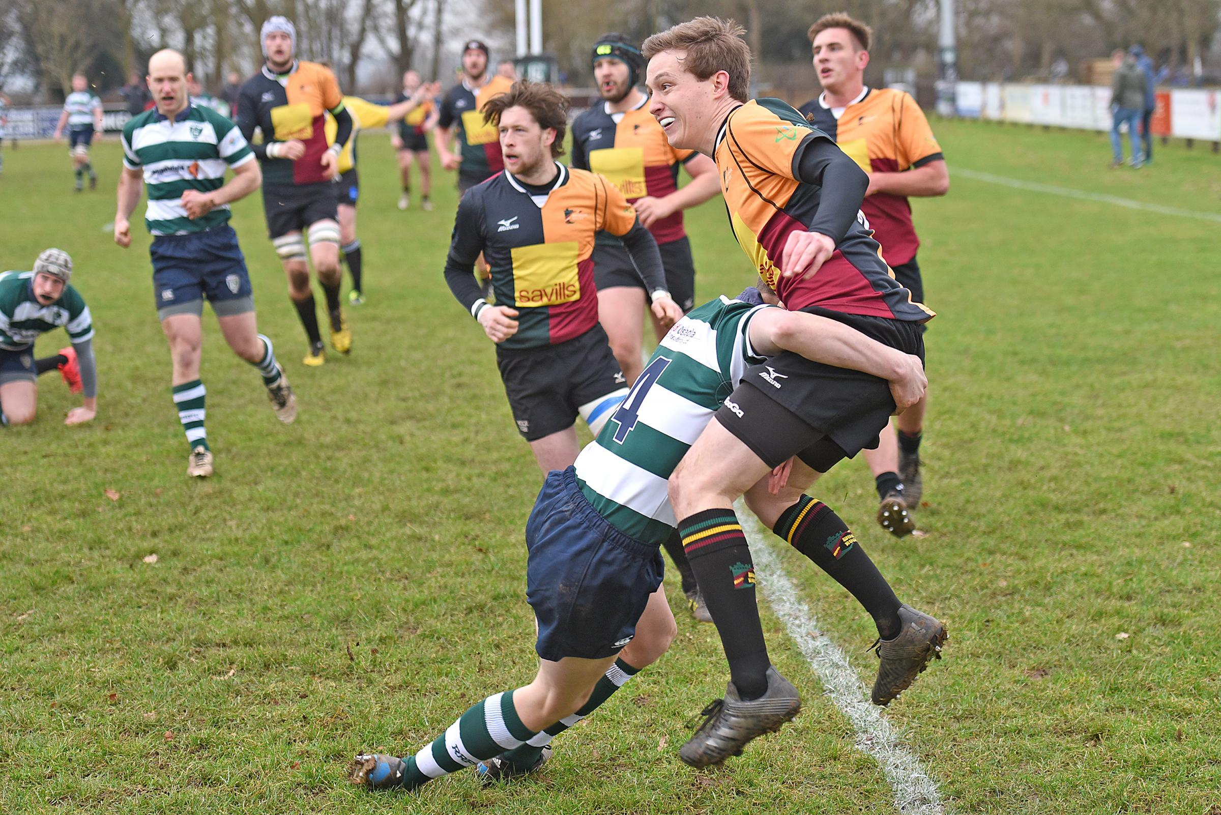Reading (green/white) make a big tackle during their heavy defeat to Windsor