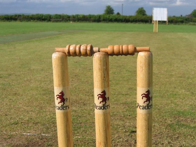 Two sets of three cricket stumps and two bails.