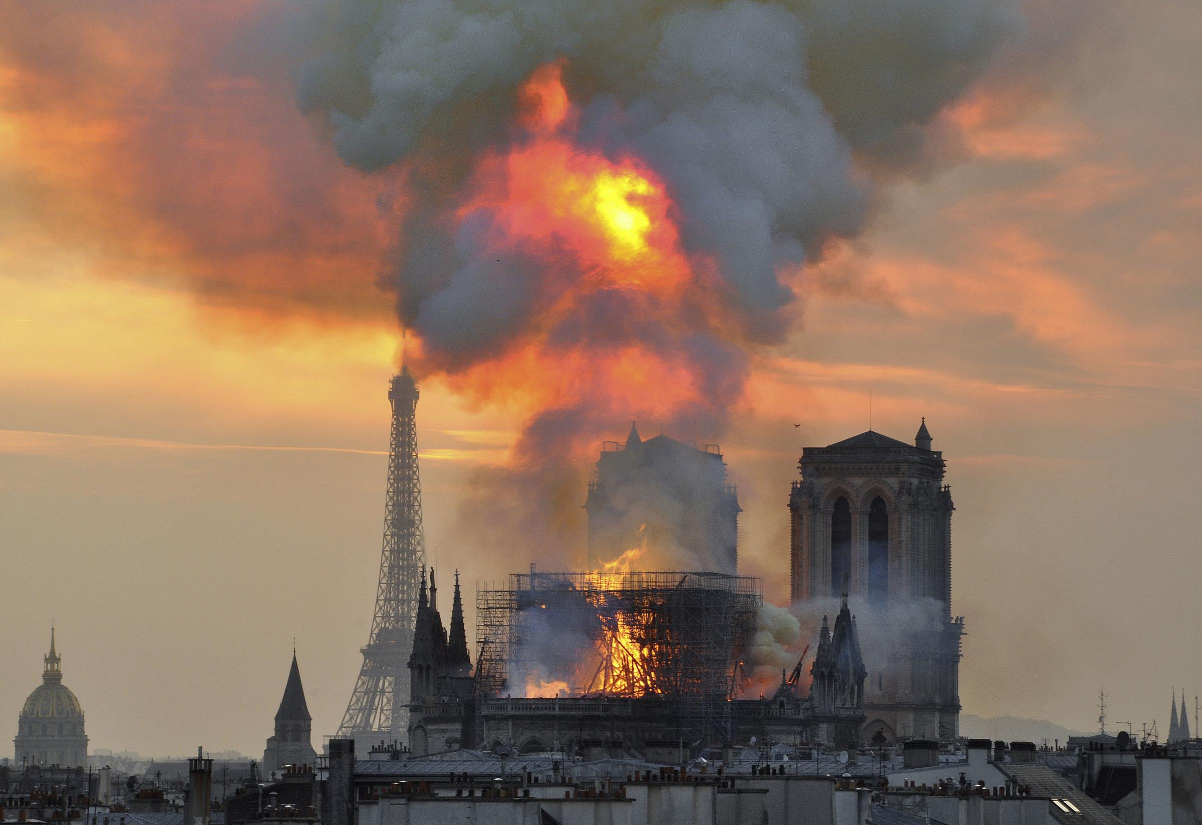 In this image made available on Tuesday April 16, 2019 flames and smoke rise from the blaze at Notre Dame cathedral in Paris, Monday, April 15, 2019. An inferno that raged through Notre Dame Cathedral for more than 12 hours destroyed its spire and its ro